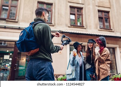 Videographer filming models on city street. Man using steadicam and camera to make footage. Digital devices for video shoot. Stock filmmaker