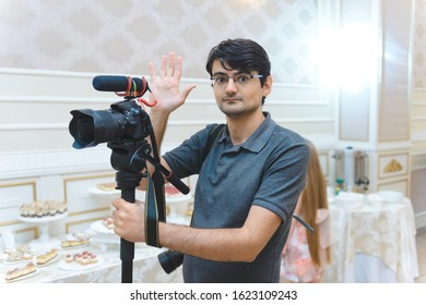 videographer with glasses waving with hand at restaurant
