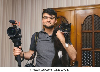 videographer holding camera and cat at room