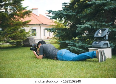 videographer laying on green grass with camera at yard