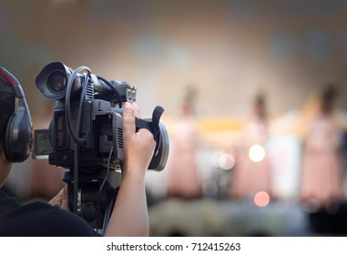 videographer man on duty with professional camcorder with blur background