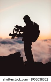 Videographer man shooting footage using dlsr camera mounted on gimbal stabilizer equipment. Video production crew for movie, cinema. Silhouette of professional filmmaker filming outdoor.