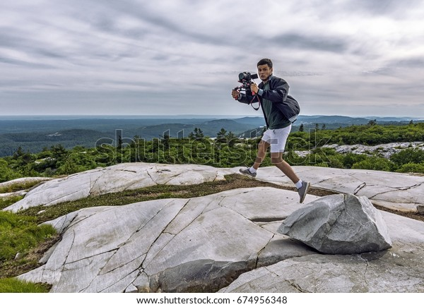 Videographer in motion, in the air, at the top of a peak, filming a scene. Green forest and lakes below.