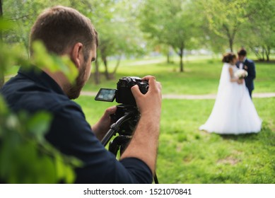 The videographer shootes the marrieds in the park in the summer.