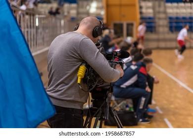 A videographer shoots a video of a sports match
