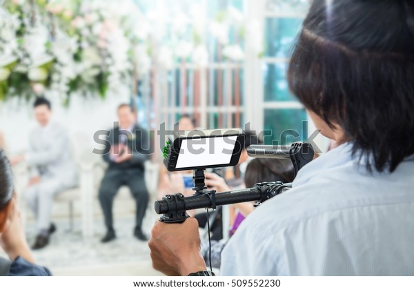 Videographer takes video camera with blank screen and blur image of group people in the background with free copy space for your text