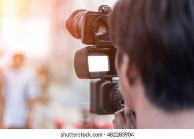 Videographer takes video camera whit white screen and blur image of group people in the background with free copy space for your text