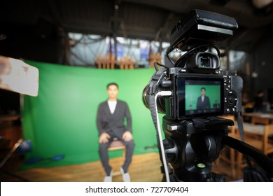 Videographer taking video camera, camera man working with professional equipment film on green screen.