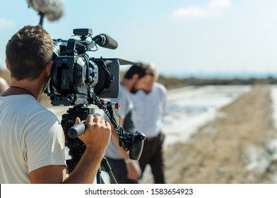 videographer with tripod camera in documentary film shooting