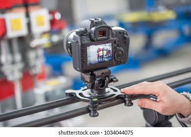 Videographer using camera slider, making video of business at factory. Close up