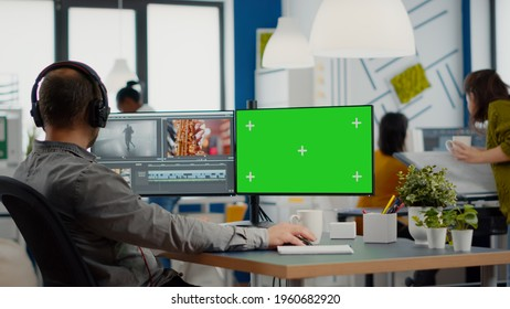 Videographer using computer with chroma key, mock up isolated display editing video and audio footage. Man editor processing film montage on pc with green screen while team working in background