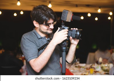 videographer working at restaurant in evening