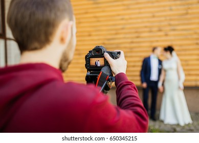 Videographer working at a wedding. Professional videographer recording wedding couple