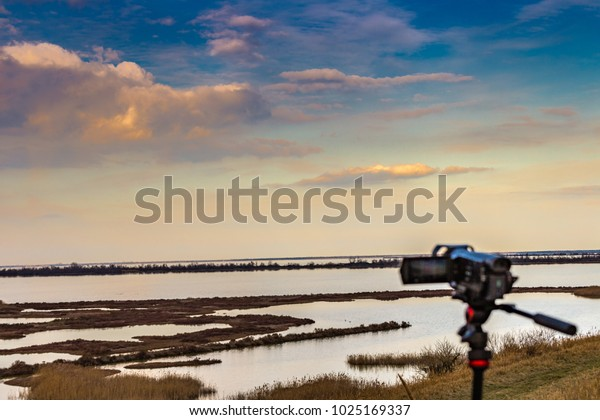 Videography from camcorder on tripod shooting cloudy sky over wild lagoon in winter