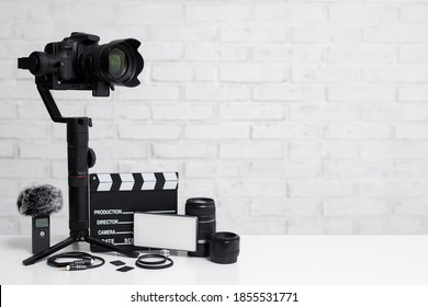 videography concept - modern dslr camera on 3-axis gimbal stabilizer, lenses, microphone, led light, clapper board and other videography equipment over white brick wall background with copy space
