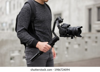 videography, filmmaking and creativity concept - close up of modern dslr camera on 3-axis gimbal stabilizer in male hands over concrete building background
