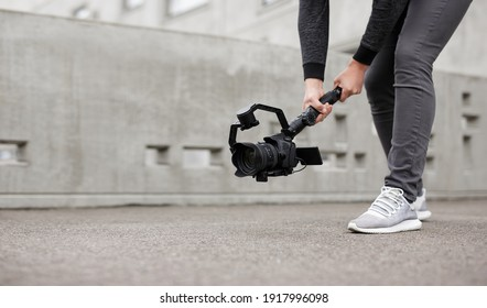 videography, filmmaking, hobby and creativity concept - close up of modern dslr camera on 3-axis gimbal stabilizer in male hands - copy space over concrete background