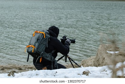 videomaker with camera on the shores of the lake in the mountains in the snow in winter - concept of documentary filmmaking in extreme conditions - passion for work