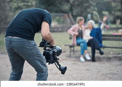 videomaker with camera in a park