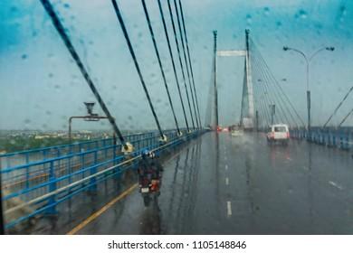 Vidyasagar Setu (Bridge) over river Ganges, known as 2nd Hooghly Bridge in Kolkata,West Bengal, India. Abstract image shot aginst glass with raindrops all over it, monsoon image of Kolkata.