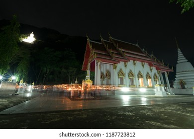 """VIEN TIEN"",Triple circumambulation, Significance in Buddhism ceremony.Peoples walking with lighted candles around pagoda in temple.Night scene with white Buddha on the mountain near the temple."