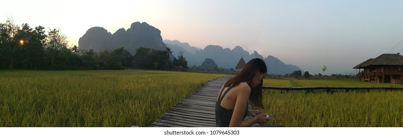VIENG TARA VILLA: VANG,LAOS -MAR 7, 2018: Woman holding smartphone on the background of the scenery wooden bridge on a green rice field and the back consists of the mountains of Vieng Tara Villa.