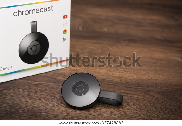 VIENNA, AUSTRIA, 09 November 2015:  2nd generation Google Chromecast HDMI-Dongle on a wooden surface with parts of its original packaging.