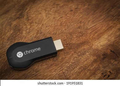 VIENNA, AUSTRIA, 10 May 2014:  Google Chromecast HDMI-Dongle on a wooden surface.