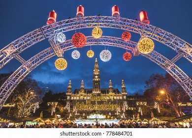 VIENNA, AUSTRIA - 17TH DECEMBER 2017: The outside of the Christmas Market at Rathaus in Vienna at night. Decorations, market stalls and lots of people can be seen.