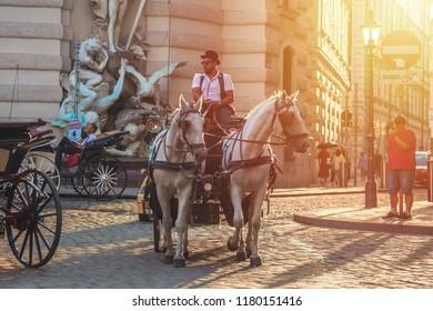 Vienna, Austria - 19.08.2018: Horse-drawn carriage or Fiaker, popular tourist attraction, on Michaelerplatz in Vienna.