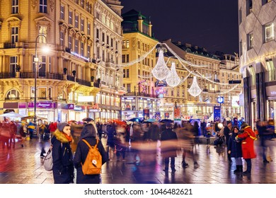VIENNA, AUSTRIA - 28 DECEMBER 2017: Rainy twilight scene at central street in Vienna, Austria. Pedestrians having stroll about shopping by Christmas decorated streets in Wien.