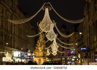 VIENNA, AUSTRIA - 2ND DECEMBER 2015: A view along Graben Street at night during the Christmas season. People, decorations and buildings can be seen. The Pestsaule memorial column can be seen.