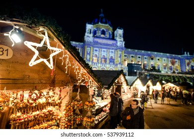 VIENNA, AUSTRIA - 6 DECEMBER 2016: People visiting Maria Theresa Square (Platz) Christmas Market. Focus in front.
