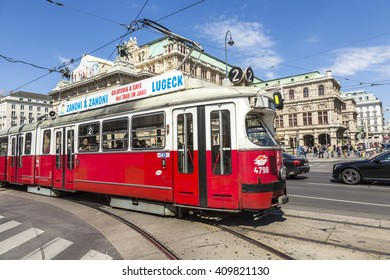 VIENNA, AUSTRIA - APR 24, 2015: people in streetcar in front of Vienna State Opera house - the Hofburg - with history dating back to mid-19th century. It is located in centre of Vienna