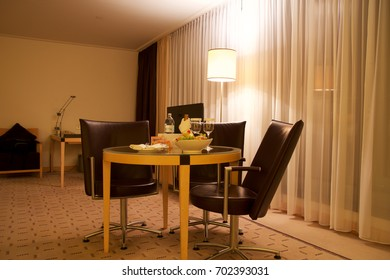 VIENNA, AUSTRIA - APR 28th, 2017: Romantic evening with bottle of red wine, sweets and fruits in the luxury hotel room on a table with three leather chairs, Hilton Penthouse Suite