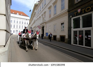 VIENNA, AUSTRIA - APRIL 11,  2018 : The driver of the fiaker with tourists in Vienna, Austria. Since the 17th century, the horse-drawn carriages characterize Viennas cityscape.