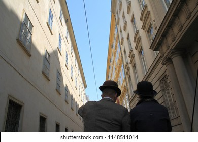 Vienna / Austria - April 13, 2009: A man and a woman in cloth of XIX century style with black hats seen from backs  between high walls of buildings around and a narrow strip of blue sky above them.