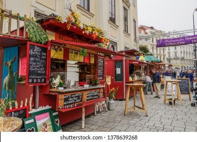 Vienna, Austria - April 14 2019: Easter open air Food Market Altwiener Freyung Ostermarkt. Crowd at Wien, Osterreich 2019 street market, where vendors from Austrian regions sell local food & drinks.