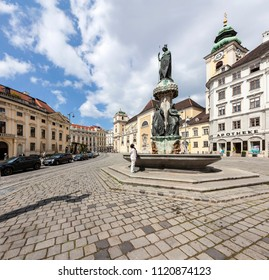 VIENNA, AUSTRIA - APRIL 19, 2015: Austriabrunnen in front of the Scottish Abbey on the square Freyung in the center of Vienna. In German language Schottenstift - is a Roman Catholic monastery founded