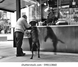 VIENNA, AUSTRIA - APRIL, 2011: Man with a big black dog standing at the street food kiosk waiting for a hot dog. Funny shadow of the dog. Black and white photo, film effect