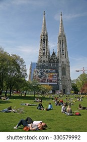 VIENNA, AUSTRIA - APRIL 22, 2010: Young people relaxing on the grass of Sigmund Freud Park near The Votive Church (Votivkirche)