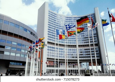 Vienna, Austria - April 24, 2015: Flags of different countries on background of The United Nations building. Headquarters of the International Atomic Energy Agency (IAEA). Vienna international center