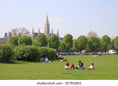 VIENNA, AUSTRIA - APRIL 25, 2013: People relaxing in a park in Vienna near Hofburg Imperial Palace with Vienna City Hall in the background