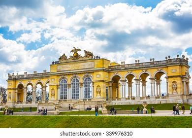 Vienna, Austria - April 3, 2015: The Gloriette in the Schonbrunn Palace Garden, Vienna, Austria against the cloudy blue sky. Tourists walking around.
