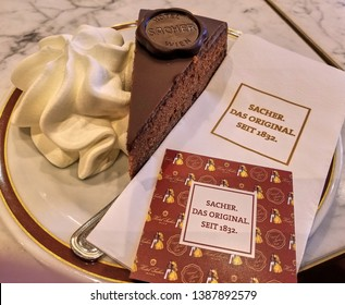 Vienna, Austria - Aug 2018: Closeup of a plate of the most famous chocolate cake in the world, the Viennese specialty Sacher Tort with real whipped cream, served at the iconic Hotel Sacher.