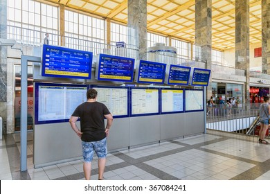 VIENNA, AUSTRIA - AUGUST 08, 2015: People Looking At Departure And Arrivals Screens In Wien Mitte Station The Major Hub For S-Bahn Suburban Trains, U-Bahn Trains And The City Airport Train (CAT).
