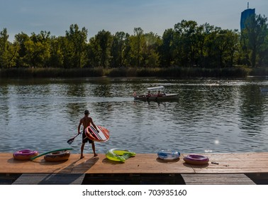 Vienna, Austria, August 2017: unknown surfer preparing to enter the water on a sunny day on Vienna's old Danube arm, where locals enjoy the weekend on the water with swim, surf and boats.