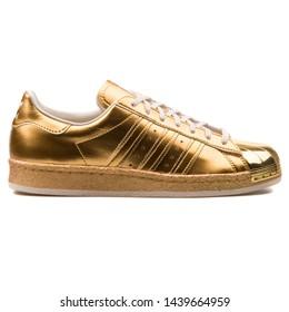 VIENNA, AUSTRIA - AUGUST 25, 2017: Adidas Superstar 80s Metallic Pac gold metallic sneaker on white background.