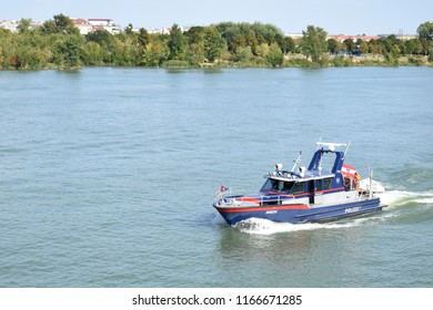 "VIENNA, AUSTRIA - AUGUST 28, 2018: Austrian police boat on the Danube River in Vienna. Donauinsel (Eng. ""Danube Island""), a popular recreational area in Vienna, in the background."