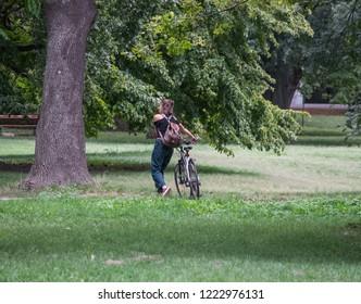 VIENNA, AUSTRIA - AUGUST 30, 2018: Girl and her bike in Vienna's prater park